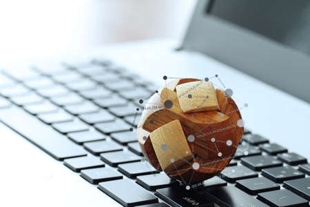 financial world: wooden texture globe with social media diagram on laptop computer as internet concept