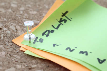 do: close up of pin and to do list word on sticky note with cork board as concept Stock Photo