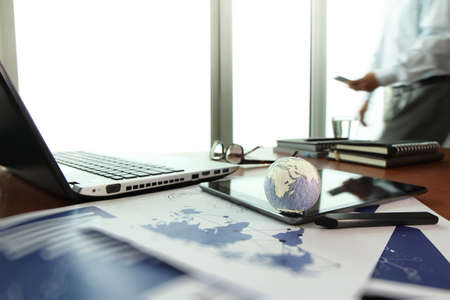 business documents on office table with texture the world on digital tablet and man using smart phone  in the background  photo