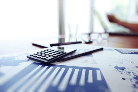 電卓とデジタル タブレットとバック グラウンドで働いていた男のオフィスのテーブルの上のビジネス文書 写真素材