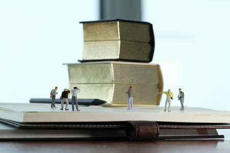 Creative idea concept - miniature photographer with vintage golden book on open paper notebook photo