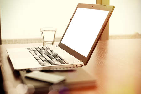 blank space: Office workplace with blank screen laptop and smart phone on wood table
