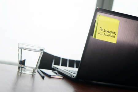 password protection: easy password on sticky note on back Laptop in office room as concept