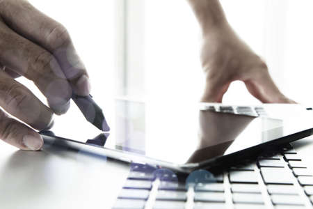 designer hand working with stylus and digital tablet and laptop on wooden desk in office photo