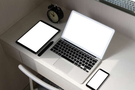 blank screen laptop computer and smart phone and digital tablet and stylus pen is on wooden desk as workplace concept photo