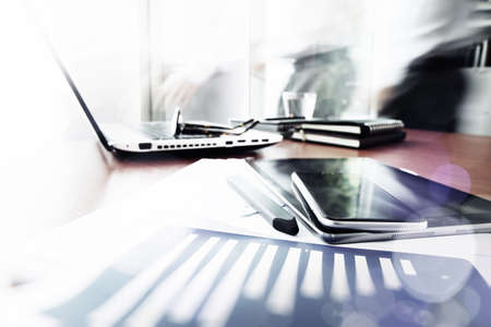 Abstract Image of business documents on office table with smart phone and digital tablet and man working in the background Banque d'images