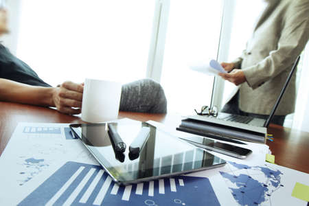 business documents on office table with smart phone and digital tablet and stylus and two colleagues discussing data in the background photo
