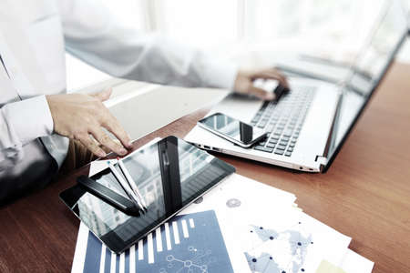 business documents on office table with digital tablet and man working with smart laptop computer background with social network diagram concept photo