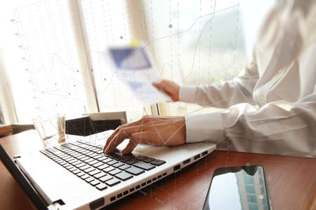 business man hand working on laptop computer on wooden desk as concept and graph business diagram photo