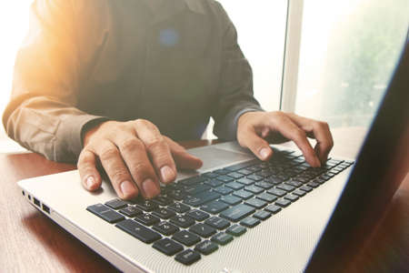 ecommerce: business man hand working on laptop computer on wooden desk as concept with overcast exposure effect