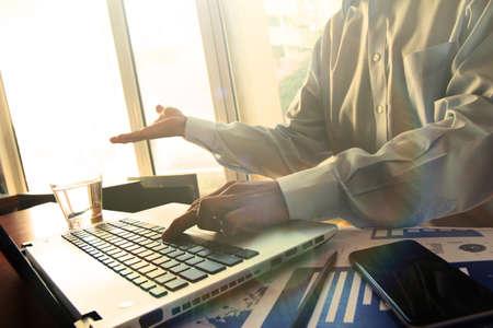 revisando documentos: Hombre de negocios de la mano, trabajando en equipo portátil en el escritorio de madera como concepto