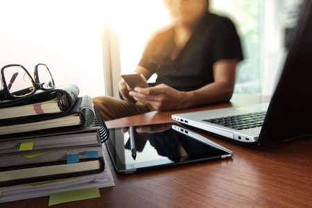 デジタル タブレットとラップトップとノートブックのスタックと目のガラス オフィスの木製の机に取り組んでデザイナーの手