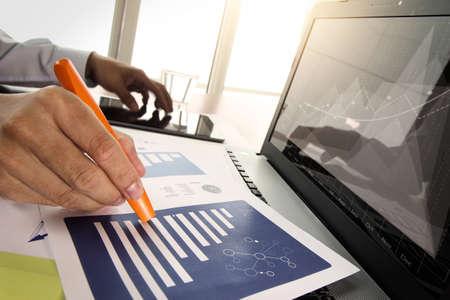 recursos financieros: documentos de negocios en la mesa de oficina con teléfono inteligente y tableta digital con el ordenador portátil y el hombre que trabaja en momento