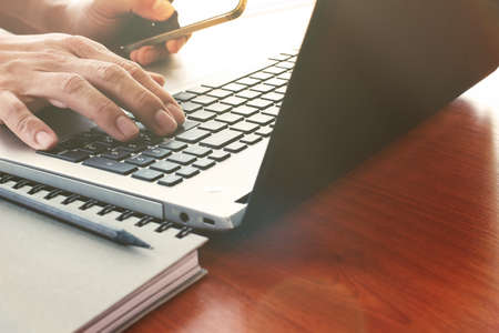 persona llamando: Primer plano de la mano del hombre de negocios que trabaja en la computadora portátil en el escritorio de madera como concepto