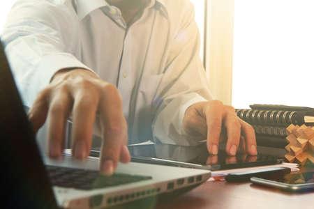trabajando en computadora: documentos de negocios en la mesa de la oficina con la tableta digital y hombre que trabaja con elegante fondo de la computadora port�til con el efecto de la exposici�n nublado