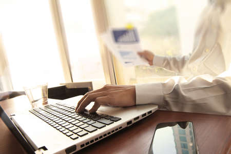 recursos financieros: Hombre de negocios de la mano, trabajando en equipo portátil en el escritorio de madera como concepto