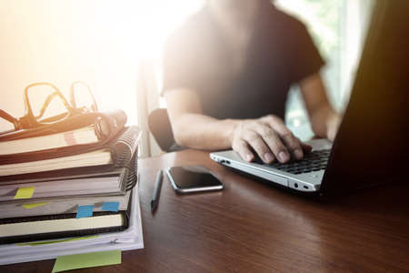 personas trabajando: diseñador de la mano de trabajo con tableta digital y un ordenador portátil y la pila cuaderno y de las gafas en la mesa de madera en la oficina