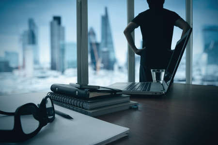 data analysis: business documents on office table with smart phone and digital tablet and london city blurred view and man thinking in the background Stock Photo