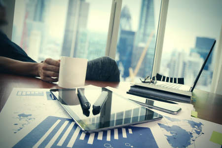 Zakelijke documenten op kantoor tafel met slimme telefoon en digitale tablet en grafiek business diagram en man werken op de achtergrond