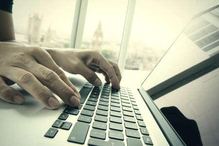 tecnología informatica: Hombre de negocios de la mano, trabajando en equipo portátil en el escritorio de madera con la ciudad de londres borrosa fondo como concepto Foto de archivo