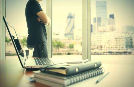 スマート フォンとデジタル タブレットとロンドン シティのオフィスのテーブルの上のビジネス文書がぼやけて表示とバック グラウンドで働いてい 写真素材