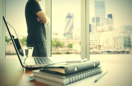 business documents on office table with smart phone and digital tablet and london city blurred view and man working in the background Stock Photo