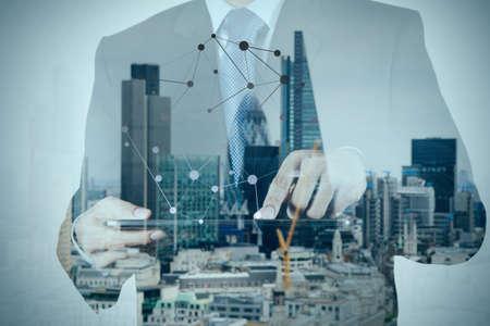 desarrollo económico: Doble exposición de éxito de negocios que usa la tableta digital con edificio de londres y el diagrama de los medios sociales