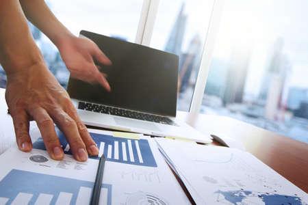 inteligencia: documentos de negocios en la mesa de oficina con teléfono inteligente y la tableta digital y diagrama de negocio gráfico y hombre que trabajan en segundo plano