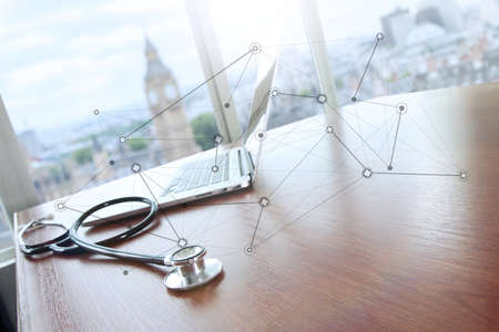 bigben: stethoscope and laptop computer on wood table and london bigben blurred background and medical network diagram