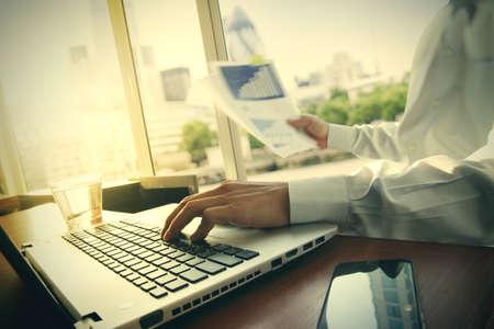 revisando documentos: documentos de negocios en la mesa de oficina con teléfono inteligente y la tableta digital y diagrama de negocio gráfico y hombre que trabajan en segundo plano