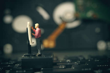 drafting table: Big data concept-miniature engineer working with drafting table with open hard disk background