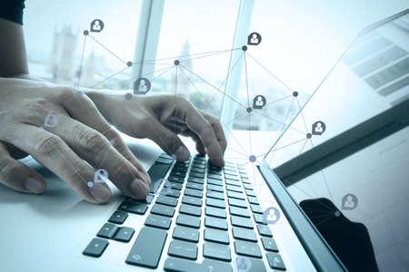personas trabajando en oficina: trabajar con documentos de negocios en la mesa de la oficina con el ordenador portátil y la ciudad de londres mano empresario borrosa fondo con el diagrama de los medios sociales