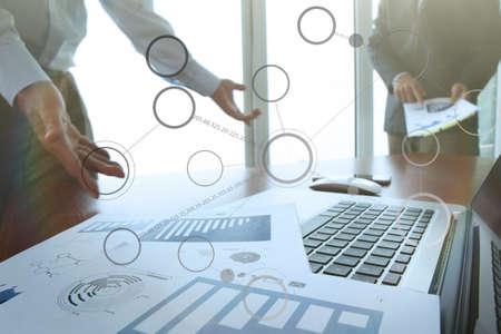 テクノロジー: スマート フォンとデジタル タブレットとスタイラスと背景のデータを議論する 2 人の同僚のオフィスのテーブルの上のビジネス文書