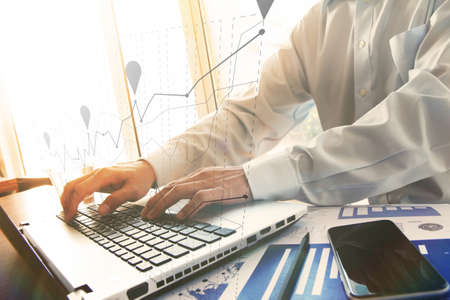 business documents on office table with smart phone and digital tablet and graph business diagram and man working in the background Stock Photo - 41474471