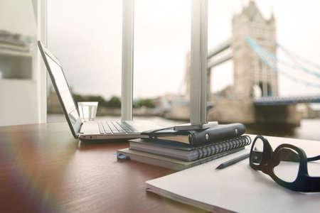 ラップトップ コンピューターは、曇り効果をもつ職場コンセプトとして木製の机の上は
