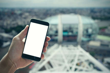 eye pad: man hand holding blank screen smartphone against london city blurred background