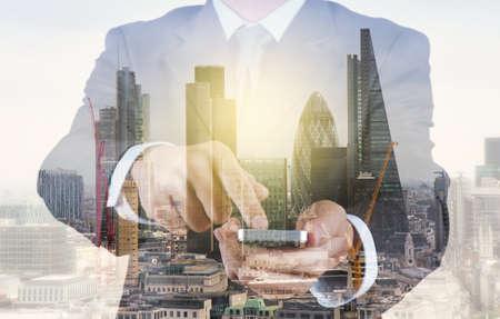 desarrollo económico: Doble exposición de negocios éxito en el uso de teléfonos inteligentes con la construcción abstracta Foto de archivo