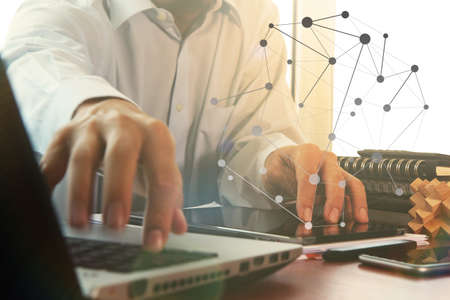 business documents on office table with digital tablet and man working with smart laptop computer background with overcast exposure effect with social media diagram photo