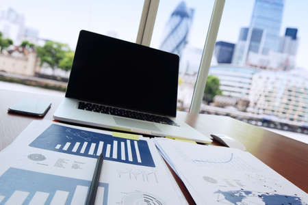 office space: business documents on office table with pen and digital tablet as work space business concept with london city blurred background