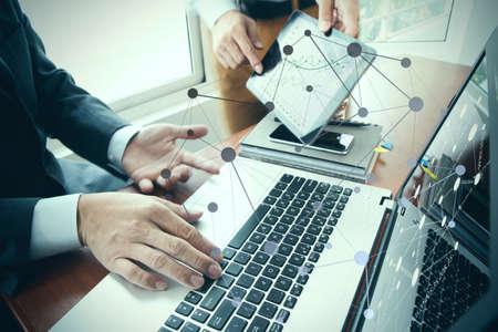 technology: documenti aziendali sul tavolo ufficio con smart phone e tablet digitale e stilo e due colleghi che parlano di dati in background