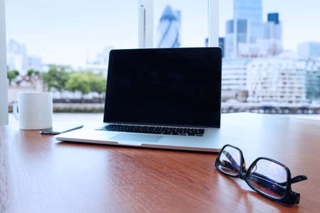 documentos de negocios en la mesa de la oficina con el ordenador portátil y el teléfono inteligente como concepto de negocio espacio de trabajo con la ciudad de londres fondo borroso