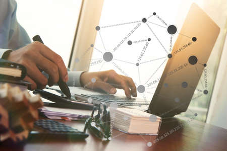 Businessman hand using laptop and mobile phone with overcast effect on wooden desk as concept with social media diagram photo