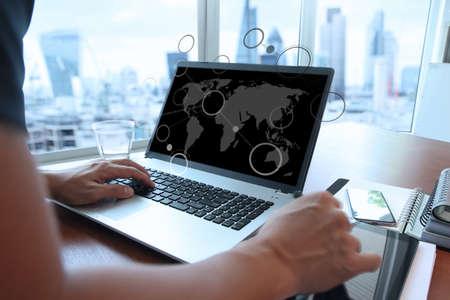 mundo manos: Primer plano de la mano del hombre de negocios que trabaja en la computadora portátil de pantalla en blanco en el escritorio de madera como concepto con el diagrama de los medios sociales