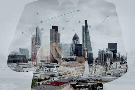 medios de comunicaci�n social: Doble exposici�n de �xito de negocios usando el tel�fono inteligente y el diagrama de los medios de comunicaci�n social con la ciudad de Londres borrosa