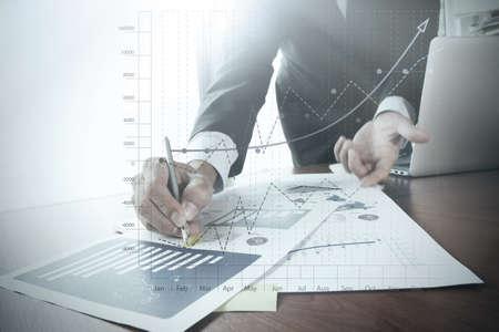 Sluit omhoog van bedrijfsmensenhand die aan laptop computer met het diagram van de bedrijfsgrafiekinformatie op houten bureau als concept werken
