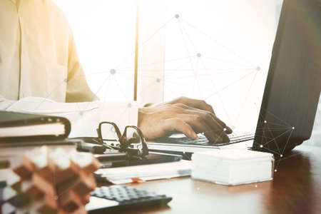 trabajo oficina: diseñador de la mano de trabajo con tableta digital y un ordenador portátil y la pila cuaderno y de las gafas en la mesa de madera en la oficina con el diagrama gráfico de negocio