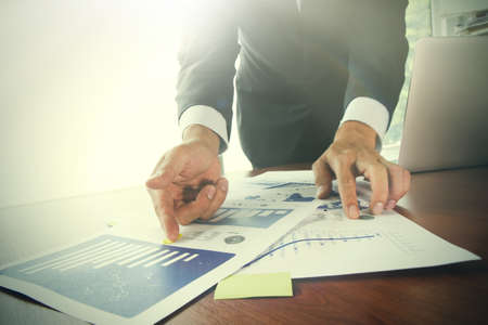 finance report: business documents on office table with smart phone and digital tablet and graph business diagram and man working in the background