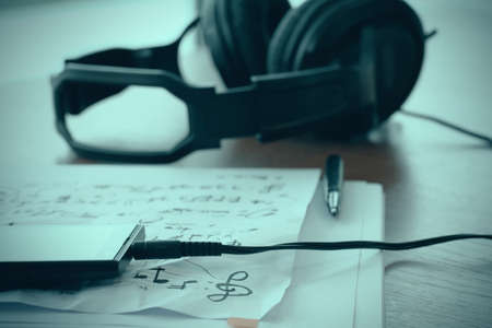 quavers: Composing music concept with shallow DOF evenly matched jack of headphone and crumpled musical notes paper