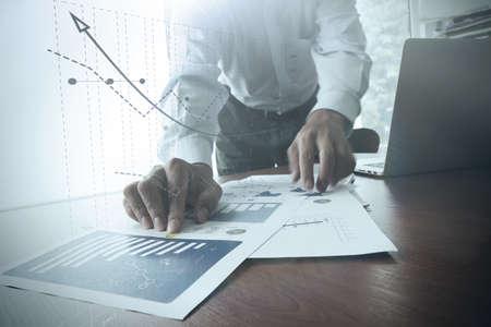 calculadora: Primer plano de la mano del hombre de negocios que trabaja en el ordenador port�til con el diagrama de informaci�n gr�fico de negocios en el escritorio de madera como concepto Foto de archivo