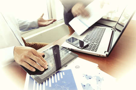 business consulting: business documents on office table with smart phone and digital tablet and stylus and two colleagues discussing data